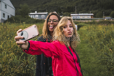 traveling friends taking smartphone selfies in