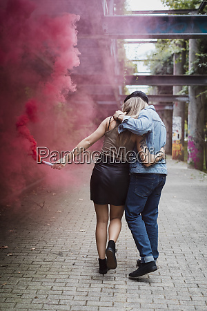young couple with smoke torch walking
