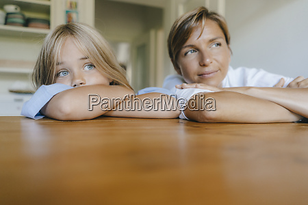 mother and daughter leaning on kitchen
