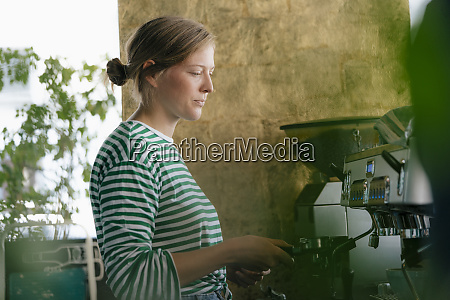 young woman preparing coffee in a