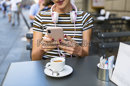 young woman using smartphone at pavement
