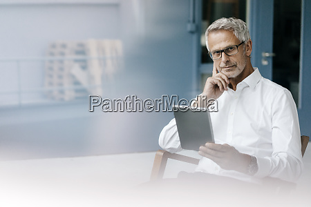 manager sitting in office using digital