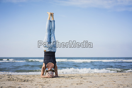 mature woman doing a headstand on
