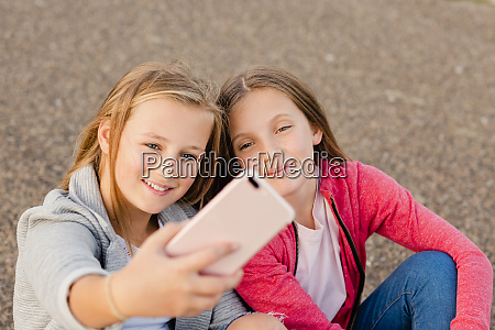 portrait of two smiling girls taking