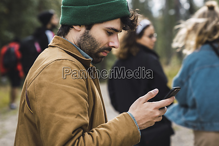 man checking cell phone outdoors with