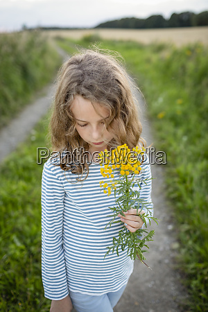 girl standing on field path holding