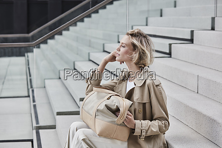 fashionable blond businesswoman wearing beige trenchcoat