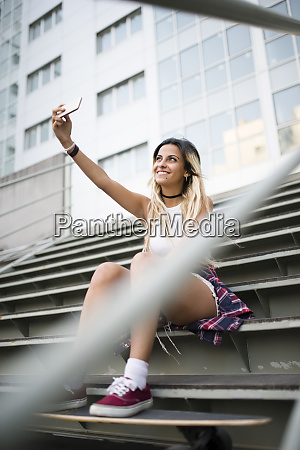 young woman sitting on stairs using