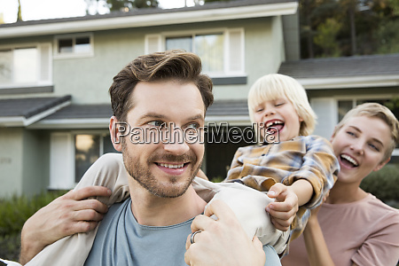 happy parents with son in front