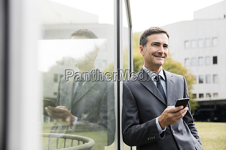 smiling businessman with cell phone leaning
