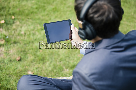 businessman wearing headphones and using tablet