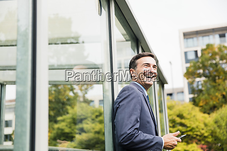 laughing businessman with cell phone leaning