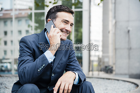 smiling businessman on cell phone in