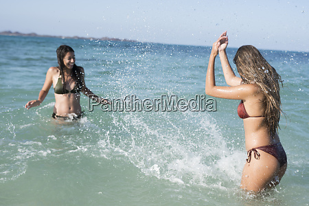 happy carefree friends splashing in the