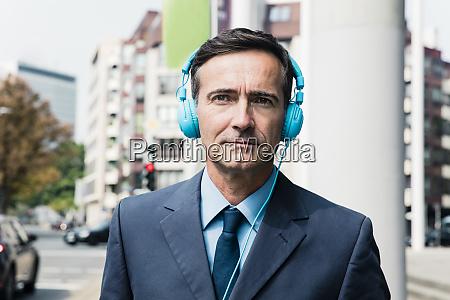 portrait of businessman with headphones in