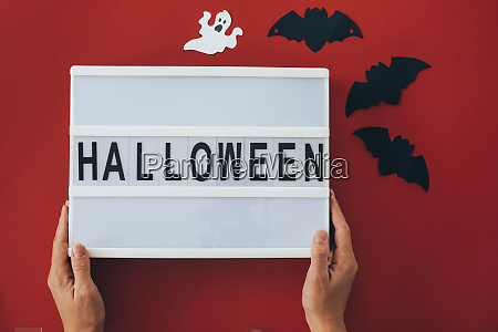womans hands holding halloween sign