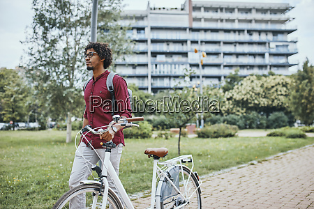 young man with backpack pushing bicycle