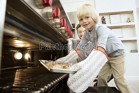 smiling boy taking baking tray out