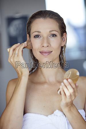 portrait of blond woman applying makeup