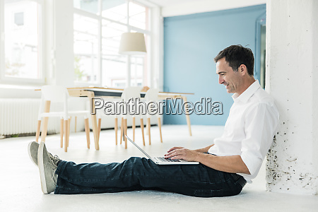 smiling businessman sitting on the floor