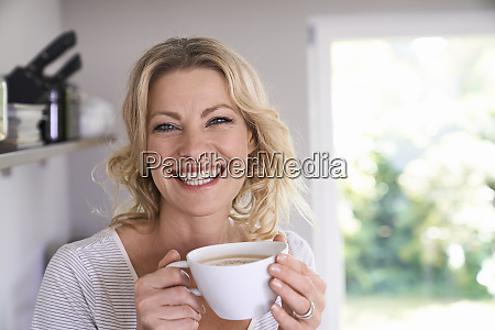 portrait of smiling woman drinking coffee