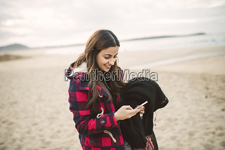 smiling young woman using smartphone on