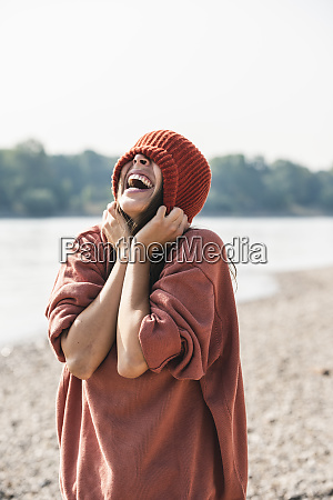 carefree young woman wearing wooly hat