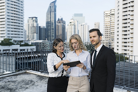 colleagues with tablet on city rooftop