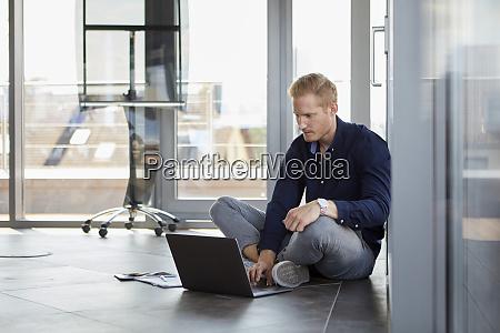 businessman sitting on the floor using