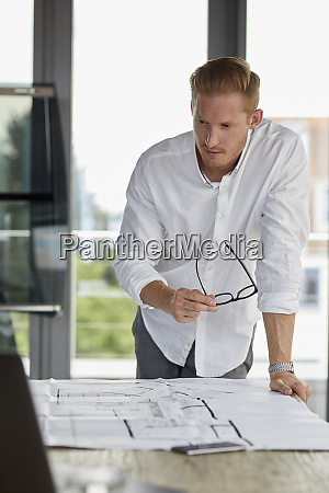 young man working on blueprint on