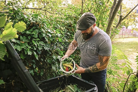 mature man discarding kitchen scraps on