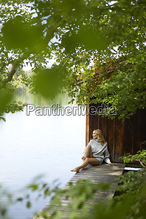 relaxed woman sitting on wooden jetty