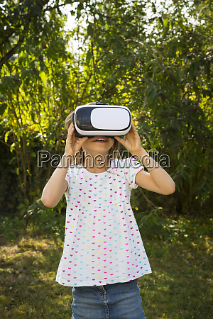 amazed little girl wearing virtual reality