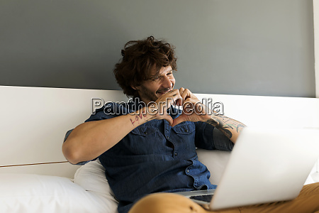 happy tattooed man with laptop chatting