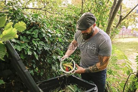 mature, man, discarding, kitchen, scraps, on - 26393515