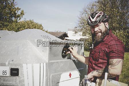 portrait of man recycling glass bottle