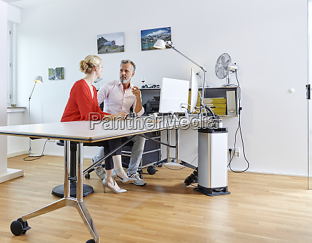 two colleagues talking at desk in