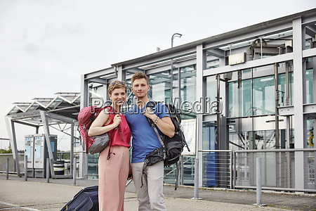 portrait of smiling couple outside airport