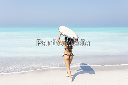 young woman carrying surfboard to the