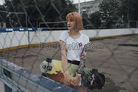 cool young woman holding carver skateboard