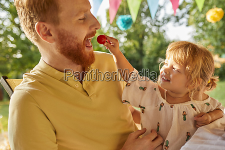 daughter feeding father with tomato on