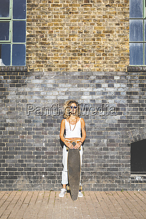 young woman standing with skateboard at