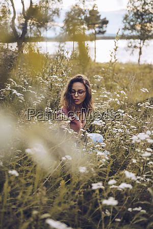 young woman crouching in flower meadow