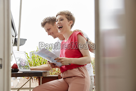 happy couple on balcony at home