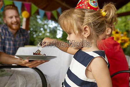 little girl eating cake on a