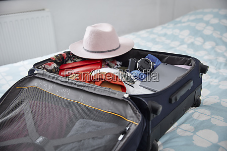 suitcase with summer vacation utensils on