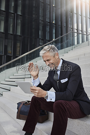 fashionable businessman with travelling bag sitting