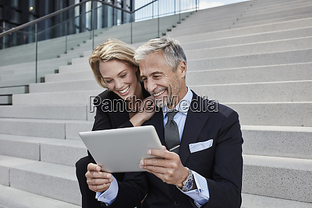portrait of two laughing businesspeople sitting