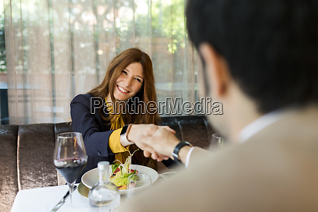 smiling woman shaking hands with man