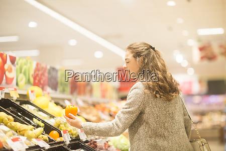 young woman choosing kaki in supermarket
